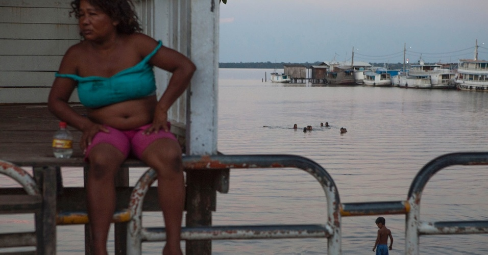 """11.ago.2013 - Mulher sobre ponte do município, com uma garrafa de cachaça (""""barrigudinha"""") ao lado, observa movimento"""