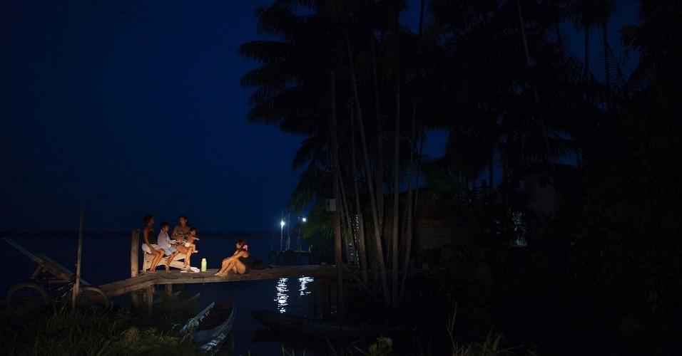 11.ago.2013 - Mulheres conversam em trapiches de madeira em comunidade ribeirinha, sob pouca ou quase nenhuma iluminação