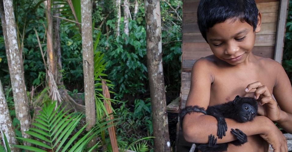 11.ago.2013 - Rodrigo Machado, 10, acaricia filhote de macaco aranha que resgatou no chão de um açaizal na cidade de Melgaço (a cerca de 300 km de Belém)