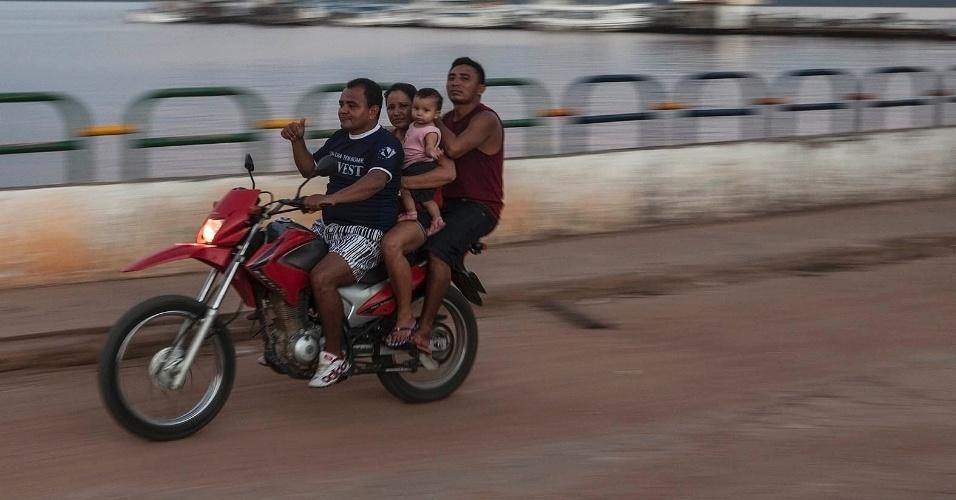 """11.ago.2013 - Sem acesso a transporte público, população de arrisca utilizando meios inadequados, como estas três pessoas e uma criança sobre uma moto. Sobre o alerta de perigo, os moradores dão de ombros: """"Não tem Detran e a polícia nunca reclamou"""""""