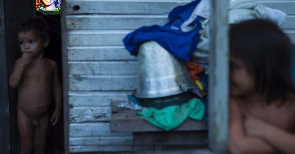 11.ago.2013 - Sem roupas e com uma televisão ligada ao fundo, garoto observa movimento dentro de casa em uma comunidade ribeirinha na cidade de Melgaço