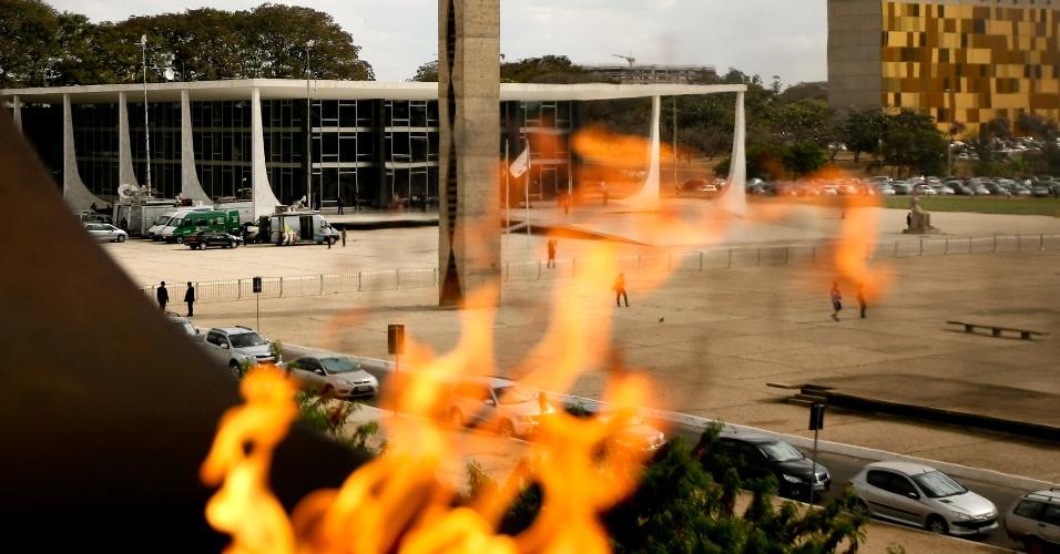14.ago.2013 - O prédio do STF (Supremo Tribunal Federal), onde acontece o primeiro dia da retomada do julgamento do mensalão, é fotografado por trás das chamas do monumento do Panteão da Pátria, na praça dos Três Poderes, na tarde desta quarta-feira (14)