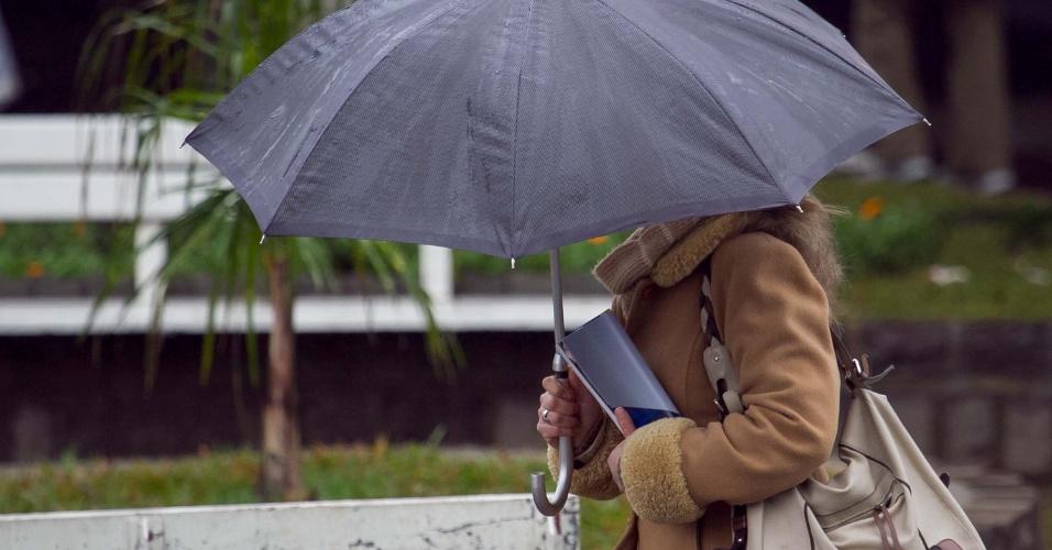 Transeuntes se protegem do frio e chuva na manhã desta quarta-feira (14), em Caxias do Sul (RS), com temperatura de 6ºC