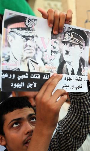 16.ago.2013 - Manifestante segura cartaz comparando Hitler ao general Abdel Fattah al-Sisi durante protesto na praça Algeria, em Tripoli, Líbia, nesta sexta-feira (16). A manifestação foi em apoio à Irmandade Muçulmana e ao presidente egípcio deposto, Mohamed Mursi