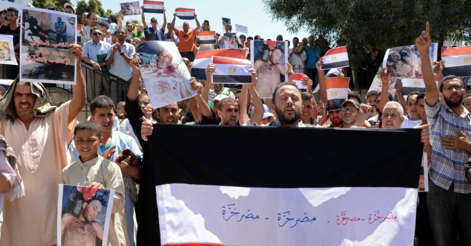 16.ago.2013 - Manifestantes marroquinos seguram fotos de vítimas do massacre ocorrido no Egito, erguem bandeiras do país e gritam palavras de ordem durante protesto contra a violência no Egito e em apoio ao presidente deposto Mohamed Mursi