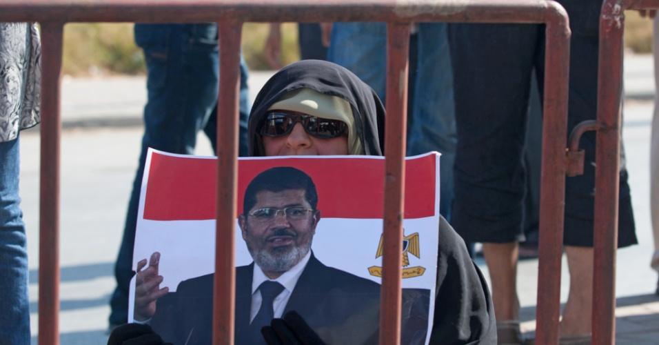 16.ago.2013 - Mulher segura cartaz com foto do presidente egípcio deposto, Mohamed Mursi, durante protesto em frente à embaixada do Egito em Túnis, na Tunísia, nesta terça-feira (16)