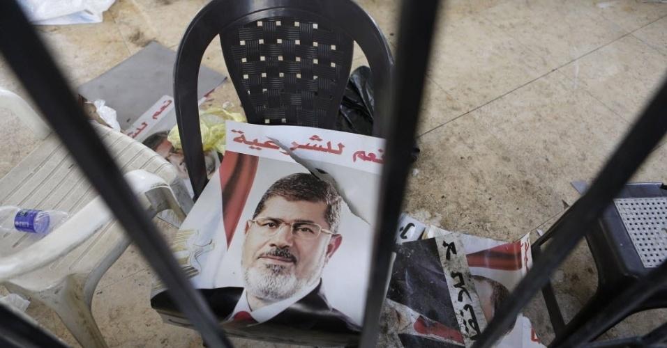 16.ago.2013 - Poster do ex-presidente deposto do Egito Mohamed Morsi é deixado em cima de cadeira na mesquita Rabaa Adawiya, que pegou fogo no Cairo, nesta sexta-feira (16)