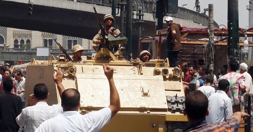 17.ago.2013 - Apoiadores do governo interino instaurado no Egito festejam a passagem de um tanque do Exército que seguia em direção à mesquita Al-Fath, na praça de Ramsés, no Cairo, neste sábado (17). Soldados egípcios invadiram o local, no qual estavam refugiados seguidores do presidente deposto Mohammed Mursi, que convocaram novas manifestações após uma sexta-feira sangrenta que deixou mais de 80 mortos