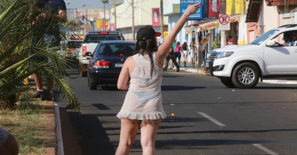 """17.ago.2013 - Mulher sinaliza para frequentadores durante """"esquenta"""", neste sábado (17), na avenida 43, em Barretos (SP), onde acontece a 58ª edição da Festa do Peão"""