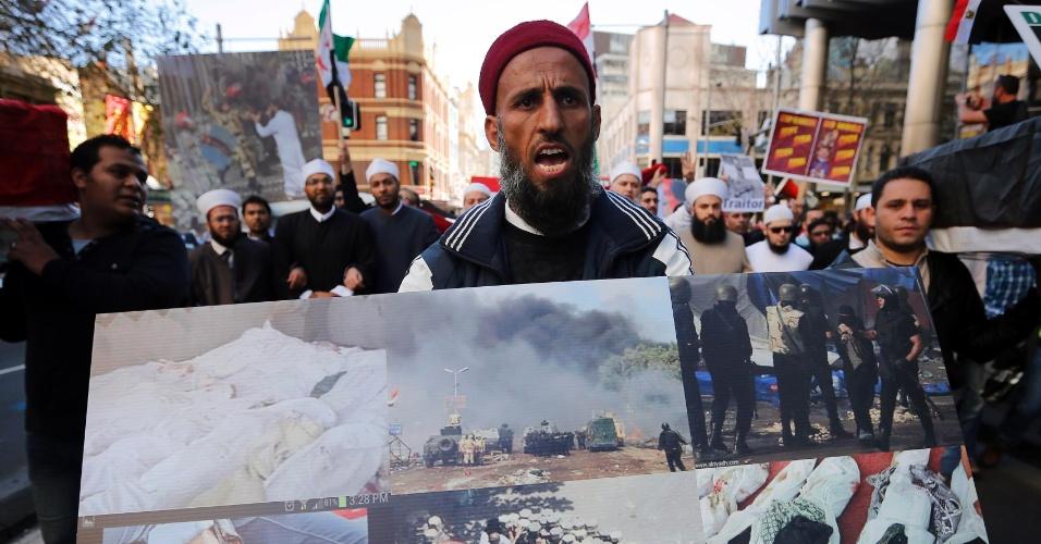 18.ago.2013 - Apoiador do presidente deposto do Egito, Mohammed Mursi, exibe cartaz com imagens trágicas dos confrontos violentos da última semana no país