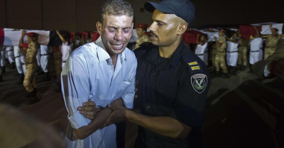 19.ago.2013 - policiais egípcios carregam caixões cobertos com bandeiras nacionais na base militar de Almaza, no Cairo, Egito. Grupos islamitas armados atacaram nesta segunda-feira dois micro-ônibus da polícia com foguetes, matando 25 policiais que iam para Rafah. Esse ataque, o mais mortífero contra as forças de ordem em décadas, eleva para 102 o número de policiais mortos em cinco dias