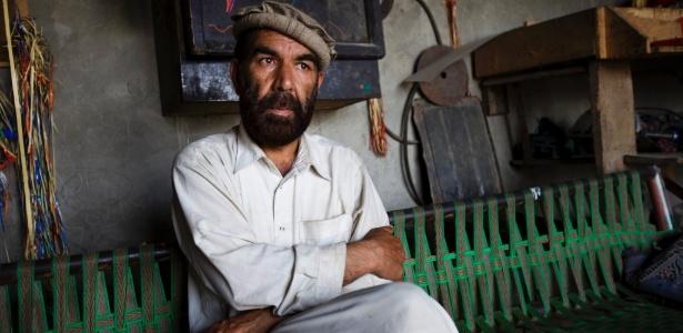 Matiullah Turab, um dos mais famosos poetas pashtuns do Afeganistão, na garagem onde ganha a vida consertando os coloridos caminhões de caravana paquistaneses