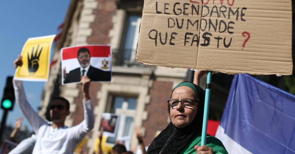 20.ago.13 - Apoiadora do presidente egípcio deposto, Mohamed Mursi, segura placa onde se lê