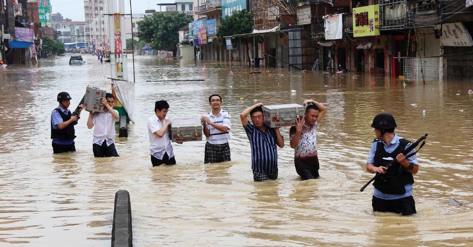"""20.ago.2013 - Chineses escoltados por seguranças armados carregam caixas com dinheiro em rua alagada de Guangzhou, que foi atingida por um tufão no último dia 15. A província chinesa é a que tem a maior perda anual projetada com enchentes até 2050, com US$ 13,2 bilhões (R$ 31 bilhões), segundo pesquisa publicada na revista """"Nature Climate Change"""". Essa e outras três cidades costeiras dos Estados Unidos (Miami, Nova York e Nova Orleans) respondem por 43% dos custos atuais das cheias, que giram em torno de US$ 6 bilhões ao ano (R$ 14 bilhões)"""