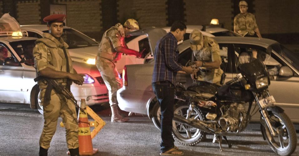 20.ago.2013 - Soldados vistoriam carro em ponto de inspeção durante período de toque de recolher no fim desta segunda-feira (19) no Cairo (Egito)