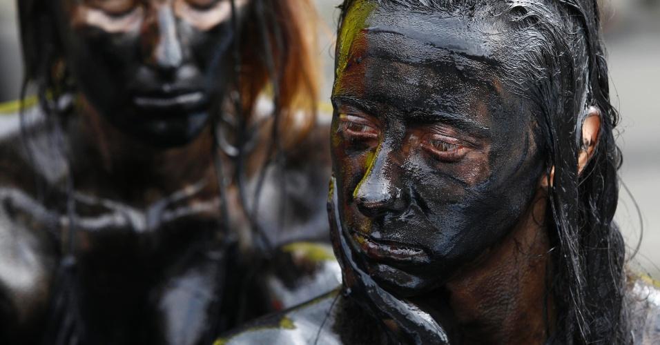 22.ago.13 - Ativistas do Greenpeace na Polônia se cobrem de tinta escura em protesto nesta quinta-feira (22) contra as gigantes de energia Shell e Gazprom, que planejam explorar óleo e gás em reservas no Ártico