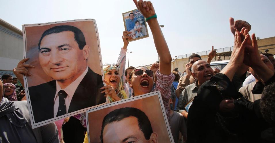 22.ago.2013 - Apoiadores do ex-presidente do Egito, Hosni Mubarak, seguram pôster com fotos dele em comemoração à liberdade concedida ao ex-ditador, que renunciou ao poder após os protestos de 2011 no país árabe. Ele foi transportado de ambulância para um hospital militar no Cairo, capital do país, nesta quinta-feira (22). Mubarak foi solto pela Justiça, que ordenou que ele cumpra prisão domiciliar