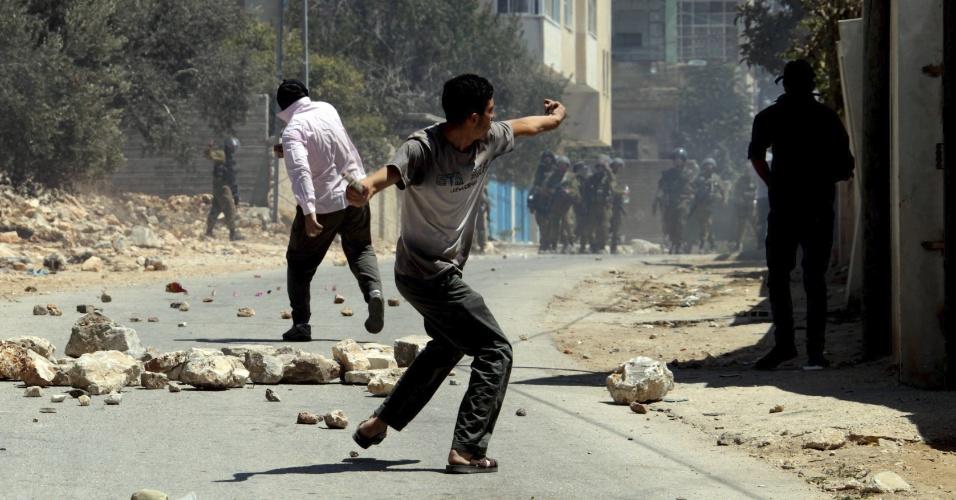 23.ago.13 - Manifestantes palestinos enfrentam soldados israelenses com pedras nesta sexta-feira (23), como parte de um protesto que acontece semanalmente contra o assentamento judaico de Qadomem, nas proximidades da cidade de Nablus, na Cisjordânia