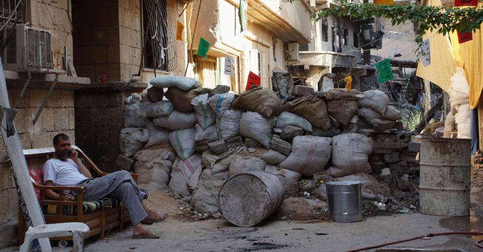 23.ago.13 - Rebelde sírio fala ao celular enquanto monta guarda atrás de uma barricada montada em rua de Deir al-Zor. Segundo estimativas da ONu, o conflito no país já deixou mais de 1 milhão de crianças refugiadas