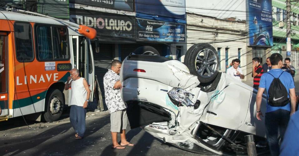 23.ago.13 - Um carro e um ônibus se envolveram em um acidente na manhã desta sexta-feira (23), no cruzamento das ruas Dr. Barros Junior e Ataíde Pimenta de Morais em Nova Iguaçu (RJ), próximo ao prédio da Prefeitura. O carro capotou, e o motorista do ônibus perdeu o controle do veículo, batendo em um poste e atingindo o muro de uma loja. Segundo o Corpo de Bombeiros, o motorista ficou ferido e foi socorrido no local