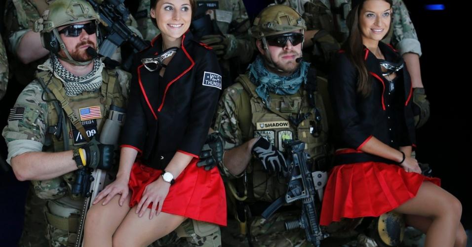 23.ago.13 - Vestidos de soldados, participantes da Gamescom, uma das maiores feiras de jogos eletrônicos do mundo, posam com modelos na abertura do evento, que acontece na cidade alemã de Colônia