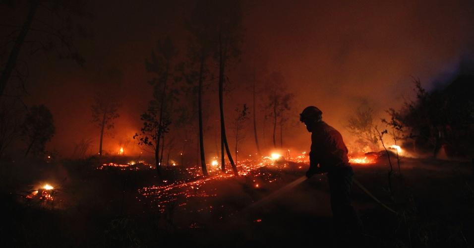 23.ago.2013 - Bombeiro combate incêndio florestal próximo à cidade de Tondela, região central de Portugal, na madrugada desta sexta-feira (23). Uma bombeira de 22 anos morreu e nove ficaram feridos, um gravemente, no combate ao um dos 13 focos de fogo que atingem o centro e norte de Portugal