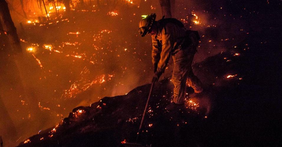 23.ago.2013 - Bombeiro varre brasas de estrada próxima à cidade de Buck Meadows, região central da Califórnia, na madrugada desta sexta-feira (23)