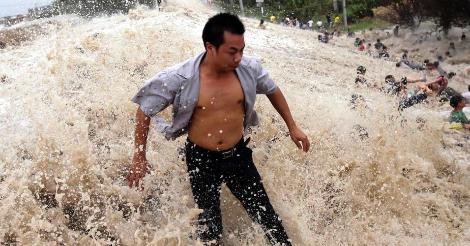 23.ago.2013 - Em imagem desta quinta-feira (22) divulgada nesta sexta (23), chineses lutam contra força da pororoca que transpõe barreira nas margens do rio Qian, em Haining, lesta da China. Com a chegada da tempestade tropical Trami, o nível do rio Qian atingiu o recorde de 6,6 metros, gerando ondas de até 1,3 m