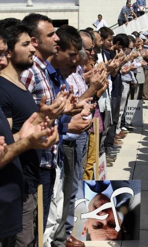 23.ago.2013 - Homens oram enquanto participam de uma manifestação contra as mortes em massa na Síria e no Egito, do lado de fora de uma mesquita em Ankara, na Turquia, nesta sexta-feira (23)