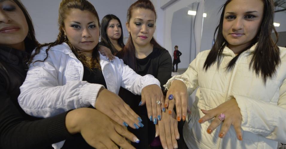 23.ago.2013 - Presidiárias mostram unhas minutos antes de um desfile na Pedras Gordas Penitenciária Modelo, a 11 km de Lima, no Peru. As mulheres, maioria presas por tráfico de drogas, desfilam utilizando modelos feitos por elas em uma oficina de costura