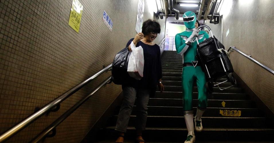 """23.ago.2013 - Tadahiro Kanemasu, também conhecido como o """"Ranger carrega-carrinho"""" leva o carro de compras de mulher em estação de metrô de Tóquio nesta sexta-feira (23). Vestido como um personagem da série Power Rangers, Kanemasu aguarda em estações de metrô para usar sua """"super força"""" no auxílio a idosos, passageiros com malas pesadas e mães com carrinhos de bebê"""