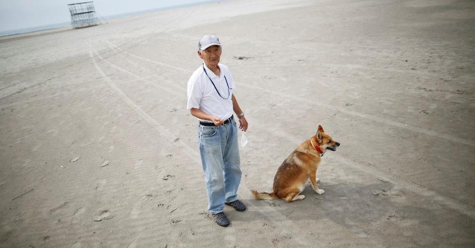 23.ago.2013 - Takeshi Takaki, 71, passeia com seu cachorro pela praia de Yotsukura, vazia, em Iwaki, cerca de 40 km ao sul da usina nuclear de Fukushima Daiichi, nesta sexta-feira (23). A praia foi aberta pela primeira vez neste verão, desde o desastre de 2011. De 100 mil visitantes no verão de 2010, a praia recebeu neste verão apenas 14 mil. Uma missão foi enviada para avaliar a gravidade do vazamento na usina depois da notícia de que água contaminada teria sido jogada no mar