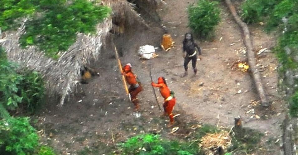 23.ago.2013 - Pesquisa aérea da Funai (Fundação Nacional do Índio) fotografa índios que vivem no meio da floresta amazônia, perto da fronteira com o Peru, em maio de 2008. Os homens da tribo apontam flechas, em uma clara demonstração de que não querem contato com outros povos