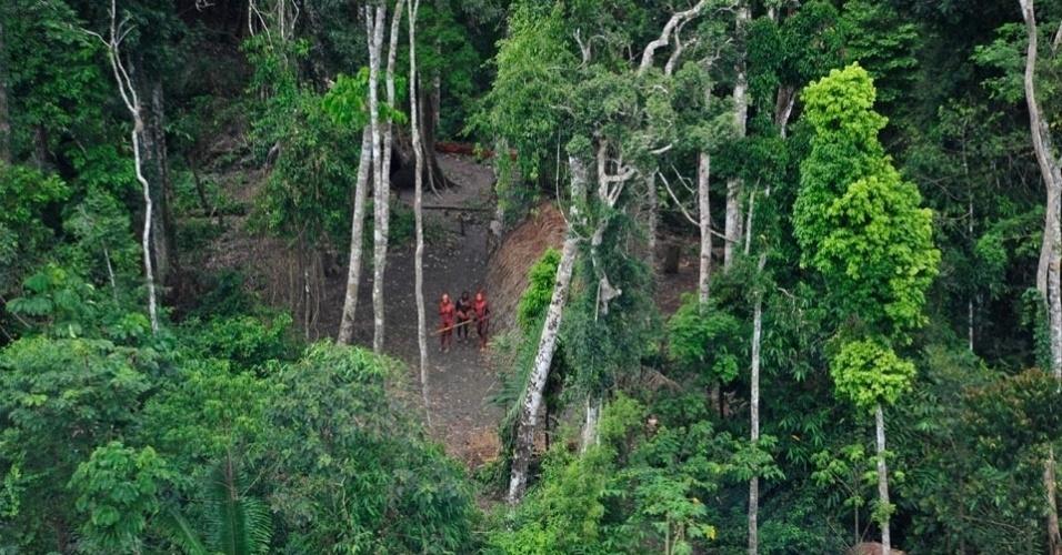 23.ago.2013 - Homens pintados com corante vegetal vermelho e preto olham para a aeronave da Funai, que fez registros da tribo isolada na Amazônia, em uma região do Brasil próxima à fronteira com o Peru