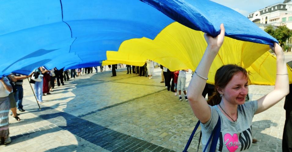 23.out..13 - Jovem segura uma bandeira gigante da Ucrânia em comemoração ao Dia Nacional da Bandeira, na capital, Kiev. No próximo sábado (24), o país comemora seu aniversário de 22 anos de independência dos russos