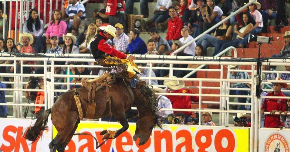 24.ago.2013 - Competidor de prova de montaria na Festa de Peão de Barretos, realizada no interior de São Paulo, se equilibra  em um cavalo bravo durante montaria