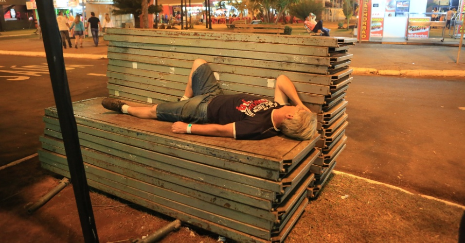 24.ago.2013 - Homem descansa em banco improvisado na Festa do Peão de Barretos (SP)