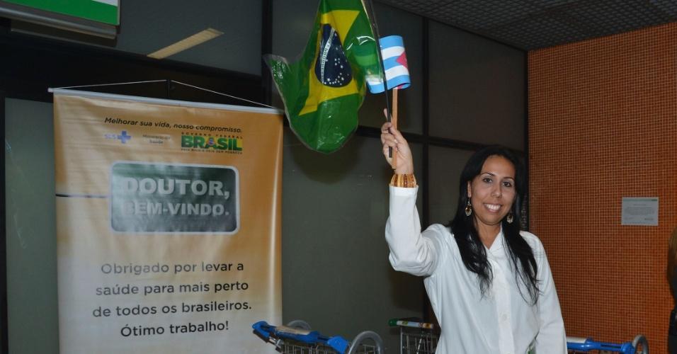 24.ago.2013 - Médica cubana segura bandeira brasileira durante desembarque no Aeroporto Internacional de Brasília