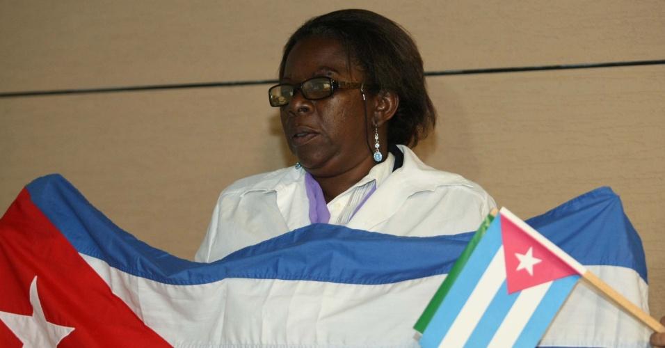 24.ago.2013 - Médica cubana Natasha Sanches exibe a bandeira de seu país ao chegar no Aeroporto Internacional de Recife, em Pernambuco. Os profissionais estrangeiros integram o programa Mais Médicos, do governo federal