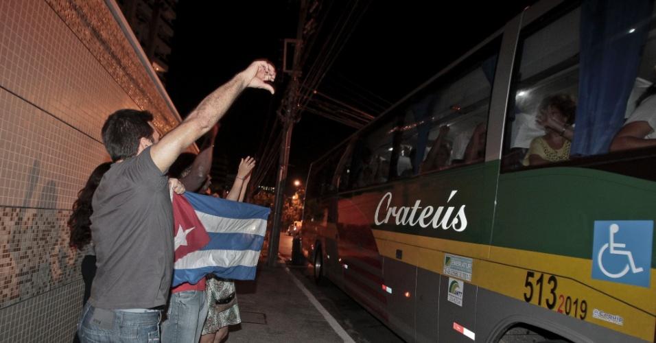 26.ago.2013 - Manifestantes a favor dos médicos cubanos balançam bandeira e acenam na noite de segunda-feira (26) durante a saída do grupo de 96 médicos estrangeiros da Escola de Saúde Pública do Ceará