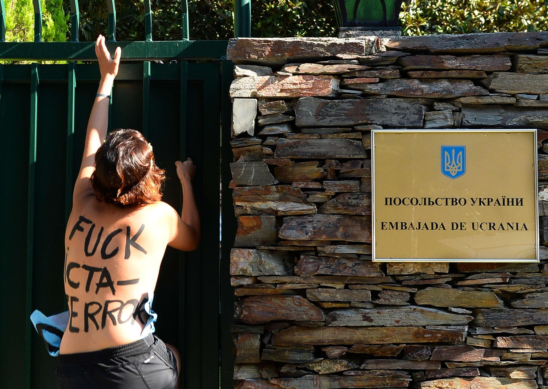29.ago.2013 - Membros do grupo feminista Femen - conhecido por suas performances de topless - tentam pular o portão da Embaixada da Ucrânia em Madri, na Espanha, contra o que elas chamam de ditadura e repressão política contra membros do grupo na Ucrânia, em frente à embaixada do país em Paris, na França. O grupo está enfrentando uma investigação criminal por posse de armas ilegais após a polícia revistar seus escritórios no centro de Kiev na terça-feira (27)