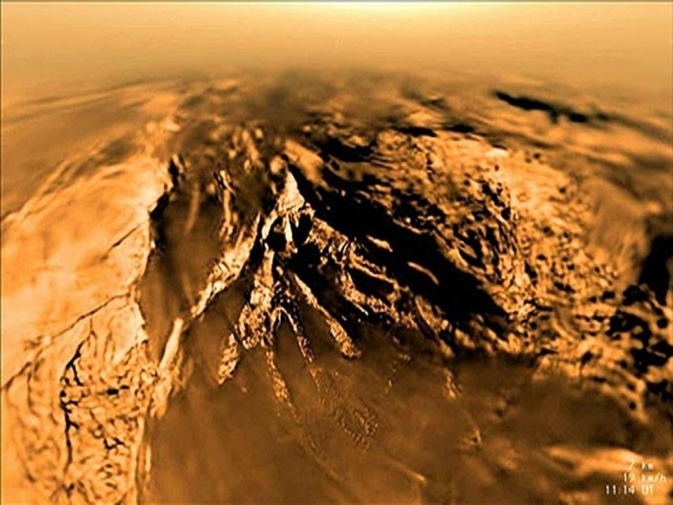 """29.ago.2013 - Uma análise detalhada da gravidade e da topografia de Titã revelou algo inesperado de uma das luas de Saturno aos cientistas da Nasa (Agência Espacial Norte-Americana). Os dados obtidos pela sonda Cassini  sugerem que o satélite tem uma camada rígida de gelo que atua como um capa na sua superfície. Para o grupo da Universidade da Califórnia, em Santa Cruz, nos Estados Unidos, o escudo gelado explica porque Titã tem um relevo pouco acidentado, sem muito vulcões - cada """"solavanco"""" no solo é compensado por uma profunda raiz de gelo que domina o efeito gravitacional do impacto na topografia lunar. As conclusões da pesquisa foram publicadas em artigo na revista Nature de quarta-feira (28)"""