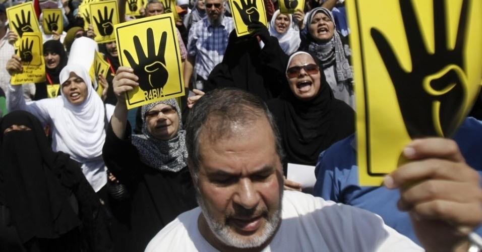 30.ago.2013 - Integrantes da Irmandade Muçulmana e opositores à deposição do presidente do Egito, Mohamed Mursi, participam de protesto no Cairo nesta sexta-feira (30). Os cartazes com a mão fazendo o número quatro são uma referência à palavra