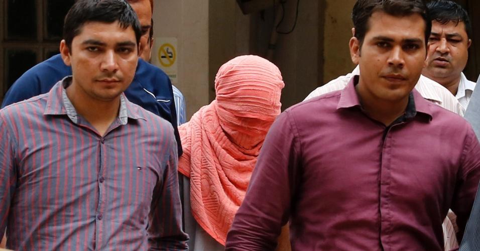 Adolescente indiano (com rosto coberto) foi condenado neste sábado (31) a três anos de detenção em uma instituição para menores, por sua participação em dezembro no estupro coletivo de uma estagiária de fisioterapia, o primeiro veredito de um caso que provocou debate sobre se a Índia é muito complacente com jovens infratores
