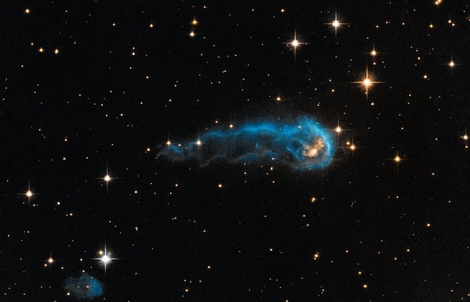 """2.set.2013 - Parecida com uma lagarta cósmica, a protoestrela IRAS 20324+4057 está bem no início de sua evolução, começando a recolher material que a cerca para """"crescer"""". Seu formato é causado pelos ventos fortes de uma estrela extremamente brilhante, que está a 15 anos-luz de distância do seu centro (a cabeça da lagarta) e emanando radiação ultravioleta, o que faz """"esticar"""" o gás e a poeira da estrela embrionária. A IRAS fica na Constelação do Cisne, a 4.500 anos-luz de distância da Terra"""