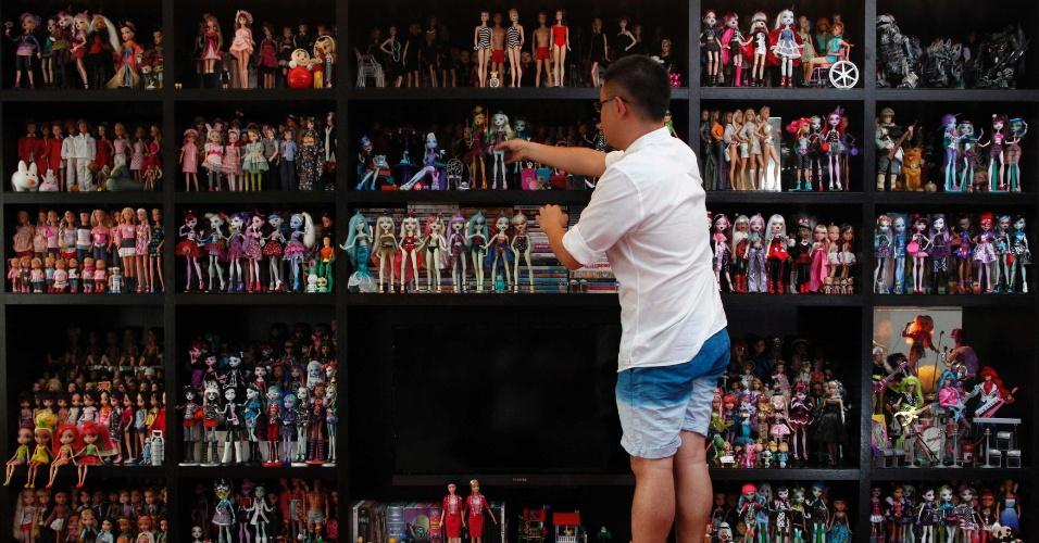 2.set.2013 - Jian Yang, um colecionador de bonecas Barbie, arruma parte de sua coleção em sua casa, em Cingapura