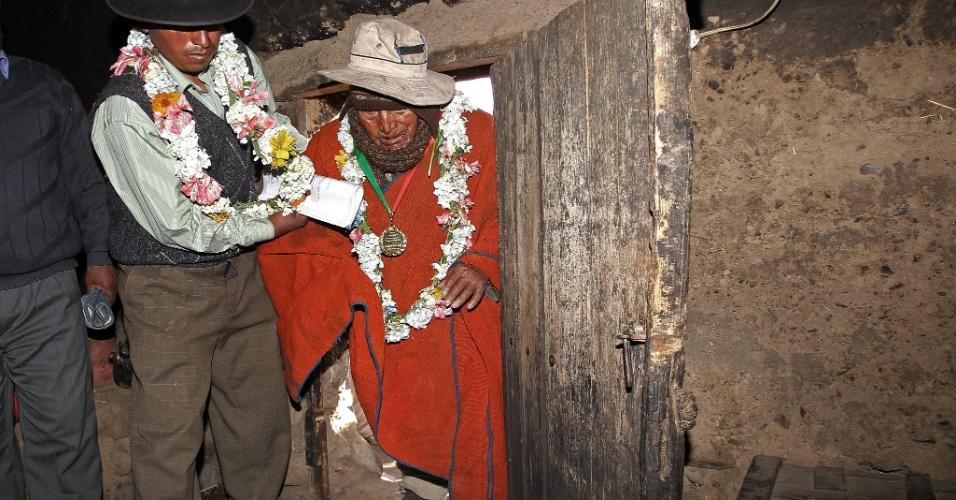 """3.set.2013 - O boliviano da etnia aimará Carmelo Flores Laura recebe ajuda para entrar em sua casa na noite desta terça-feira (3), em povoado a cerca de 70 km de La Paz, após ser condecorado como o homem mais velho do mundo. Com 123 anos, Flores recebeu a condecoração """"Tiahuanaco"""" do governador da província de La Paz, César Cocarico, e as autoridades planejam incluí-lo no livro Guinness dos Recordes"""