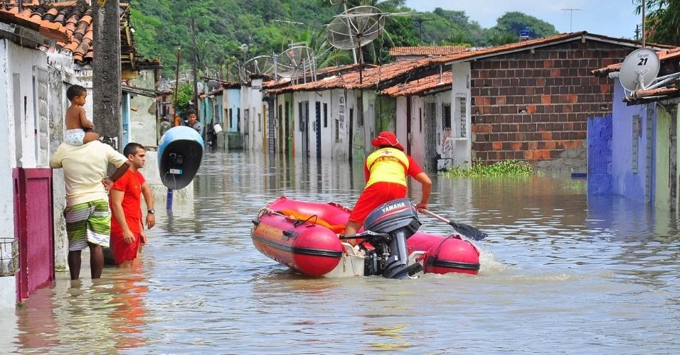 4.set.2013 - Bombeiro aproxima barco de dois moradores que aguardam resgate em bairro que ficou isolado após as fortes chuvas sobre João Pessoa (PB), nesta quarta-feira (4)
