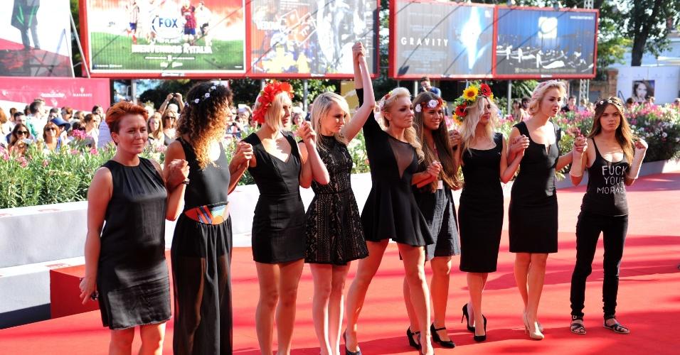 5.set.2013 - Ativistas do grupo feminista ucraniano Femen, famoso por seus protestos de topless, são fotografadas junto à cineasta Kitty Green (4ª à esquerda) no tapete vermelho do 7º Festival de Cinema de Veneza, na Itália, nesta quinta-feira (5). Green dirigiu o documentário