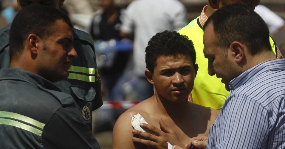 5.set.2013 - Civil ferido é atendido por equipe médica após atentado contra o ministro do Interior egípcio, Mohammed Ibrahim, no distrito de Nasser, no Cairo, Egito, nesta quinta-feira (5)